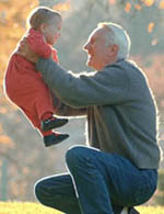 Picture of a grandfather lifting his grandson, smiling