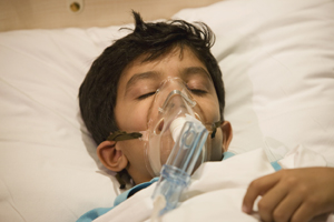 Boy resting in a hospital bed with an oxygen mask.