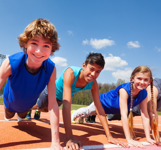 Teens smiling, ready to do push-ups outdoors