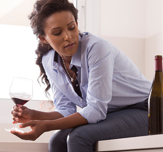 Woman holding glass of wine and looking at a wine bottle